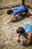 Färdig man- och kvinnakrypning under det netto under hinderkurs Arkivfoto