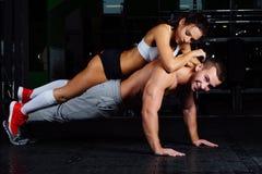 Färdig man som gör push-UPS med kvinnan på baksida i natur Arkivbilder