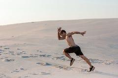 Färdig manspring som är snabb på sanden Kraftig löpareutbildning som är utomhus- på sommar Royaltyfria Foton