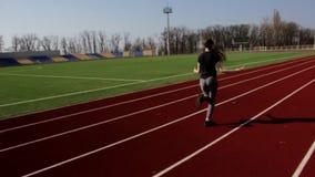 Färdig nätt ung aktiv idrottsman nenflickabanhoppning med överhopprepet som utarbetar uppvärmning på stor stadion i ultrarapid stock video