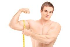 Färdig shirtless grabb som mäter hans muskel arkivbild