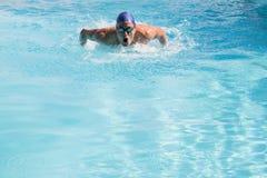 Färdig simmare som gör fjärilsslaglängden i simbassängen Arkivbilder