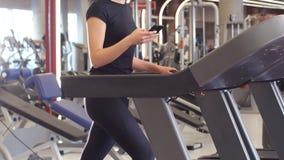 Färdig sportig affärskvinna som smsar på smartphonen, medan jogga på trampkvarnen lager videofilmer