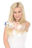 Färdig sund lycklig ung blond kvinna som rymmer en flaska av mineralvatten royaltyfria bilder