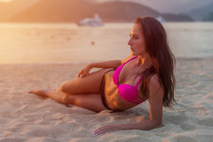 Färdig ung brunettkvinna i swimwear som ligger på stranden som solbadar i inställningssolen Royaltyfri Fotografi