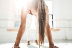 Färdig ung idrotts- kvinnlig görande genomkörare som förbättrar hennes abs i soligt vitt gummi i morgonen royaltyfria bilder
