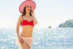 Färdig ung kvinna för innegrej som talar på mobiltelefonen på stranden royaltyfria foton
