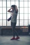 Färdig ung kvinna i idrottshallen som sätter på hoodien, medan gå Arkivbild
