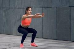 Färdig ung kvinna som gör squats arkivfoton