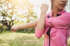 Färdig ung kvinna som gör utbildningsgenomkörare i morgon Ung lycklig asiatisk kvinna som sträcker på parkera efter en rinnande g royaltyfri bild