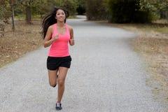 Färdig ung kvinna som joggar på en landsväg arkivbild