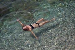 Färdig ung kvinnlig simning i genomskinligt havsvatten arkivfoton