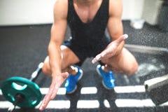 Färdig ung man i idrottshall med skivstånger som suddar hans händer med magnesium royaltyfria bilder