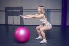 Färdig ung nätt kvinna som gör squatsövningar med konditionbollen Slapp fokus royaltyfria foton