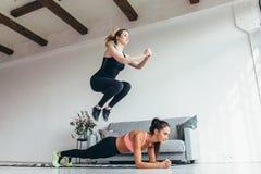 Färdiga kvinnor som hem utbildar Flicka som hoppar över hennes vän medan kvinna som utför plankaposition Royaltyfri Fotografi