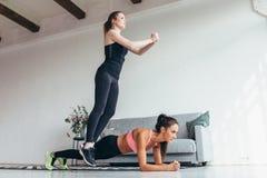 Färdiga kvinnor som hem utbildar Flicka som hoppar över hennes vän medan kvinna som utför plankaposition Arkivfoto