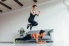 Färdiga kvinnor som hem utbildar Flicka som hoppar över hennes vän medan kvinna som utför plankaposition Arkivfoton