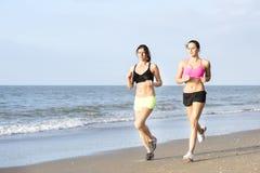 Färdiga kvinnor som joggar på stranden royaltyfri bild