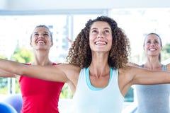 Färdiga kvinnor som ser upp och ler med utsträckta armar Arkivfoton