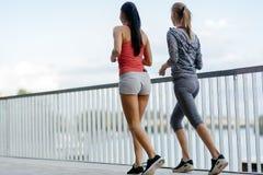 Färdiga kvinnor som utomhus joggar Fotografering för Bildbyråer