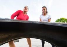 Färdiga kvinnor som utomhus lyfter gummihjulet Arkivbilder