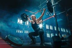Färdiga lyftande skivstånger för ung kvinna som utarbetar i en idrottshall arkivbilder
