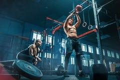 Färdiga lyftande skivstånger för ung man som utarbetar i en idrottshall arkivfoto