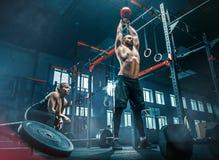 Färdiga lyftande skivstånger för ung man som utarbetar i en idrottshall royaltyfri fotografi