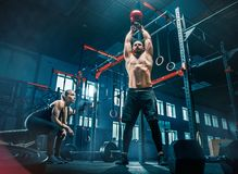Färdiga lyftande skivstånger för ung man som utarbetar i en idrottshall royaltyfri bild