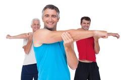 Färdiga män som sträcker deras armar Arkivfoto