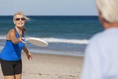 Den höga mankvinnan kopplar ihop frisbeen på stranden Royaltyfria Foton