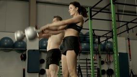Färdiga par som squatting med kettlebells lager videofilmer
