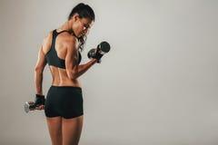 Färdiga starka lyftande vikter för ung kvinna Arkivfoton
