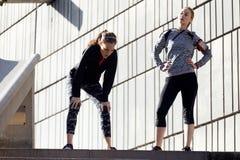 Färdiga två och sportiga unga kvinnor som kopplar av efter, utarbetar i PA Arkivbild