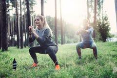 Färdiga unga Caucasian kvinnor som bär jumpsuits som utarbetar i skogen som gör squats i ottan royaltyfri foto