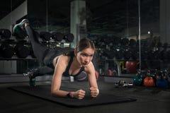 Färdiga ungdomarsom gör liggande armhävningar i en idrottshall som ser den fokuserade ursnygga brunetten som värmer upp och gör s royaltyfria bilder