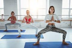Färdiga vuxna kvinnor som öva yoga, poserar i konditiongrupp Grupp av den sunda starka kvinnlign som gör färdiga övningar i den v arkivfoto