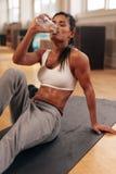 Färdigt dricksvatten för ung kvinna i idrottshallen Arkivbild