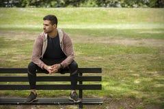 Färdigt sammanträde för den unga mannen på bänk parkerar in Arkivbild