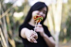 Färg för form för sötsakgodishjärta som är full i handkvinnor på suddig bakgrund, fastställd godis av färgregnbågeklubbor, gåva f royaltyfri fotografi
