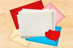 Färg märker kuvert med röda hjärtor över trätextur royaltyfri fotografi