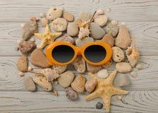Färg och skal för solglasögon orange, havsstenar och en sjöstjärna på Arkivbilder