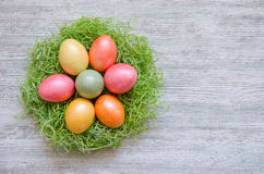 Färga ägg i rede på tappningträbakgrund Royaltyfria Bilder