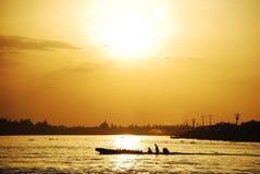 Färga bilden av folk i ett fartyg på en flod på solnedgången royaltyfria bilder