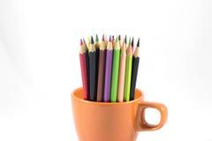 Färga blyertspennan i kaffekopp på den vita bakgrunden Arkivfoton