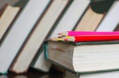 Färga blyertspennor och böcker Fotografering för Bildbyråer