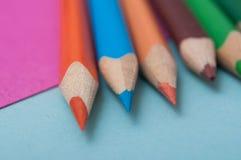 Färga blyertspennor på färgbakgrund arkivfoto
