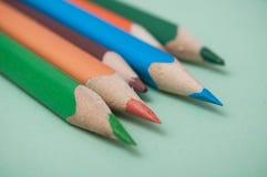 Färga blyertspennor på färgbakgrund arkivfoton