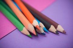Färga blyertspennor på färgbakgrund royaltyfri fotografi