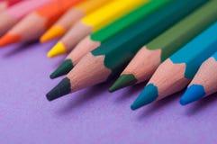 Färga blyertspennor på färgbakgrund royaltyfria foton
